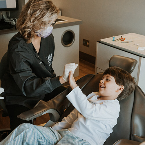 Our assistant high-fiving a young patient while they sit in the dentist chair