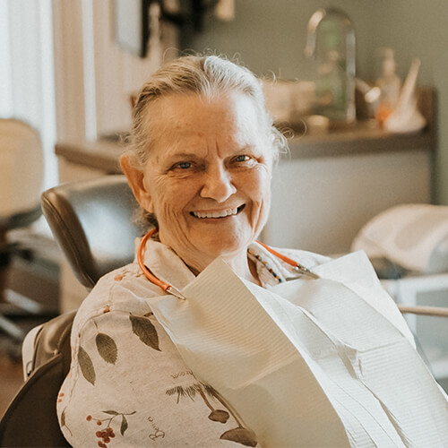 An older female patient smiling while sitting in the dentist's chair and wearing a dental bib