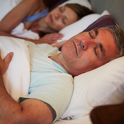 An older man sleeping in his bed with his wife behind him