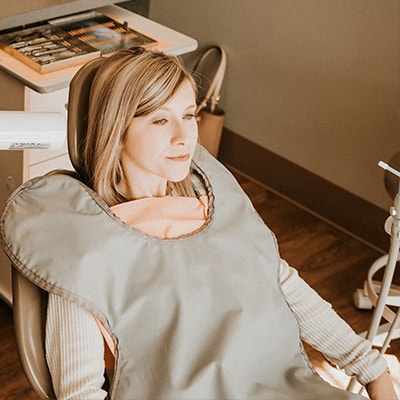 A family dentistry patient sitting in the dentist's chair while smiling
