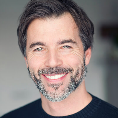 An older man with a beard smiling while wearing a black sweater