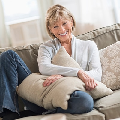 An older woman sitting on a sofa while smiling and hugging a cushion