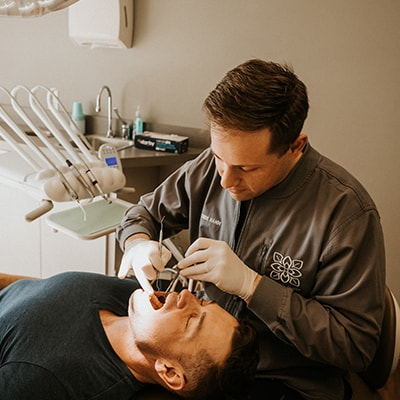 Dr. Hamm performing family dentistry on a male patient who is lying in the chair