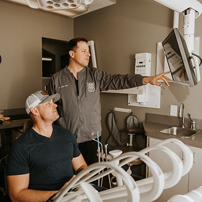 Dr. Hamm showing a male patient how his restorative dentistry treatment will work