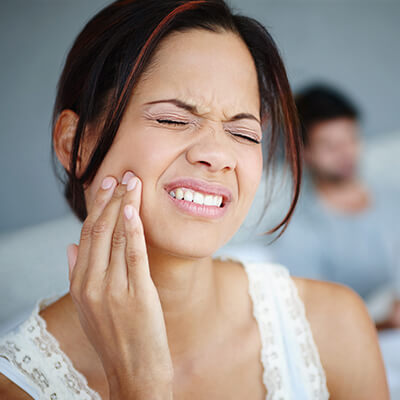 A female patient hold her jaw in pain
