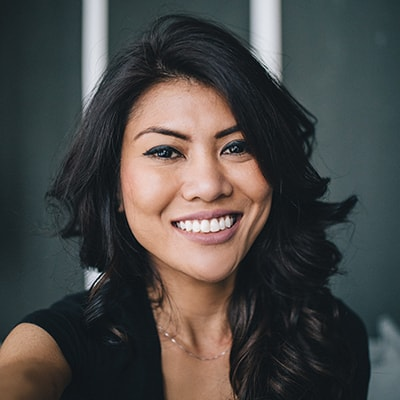 A woman smiling in a black dress after receiving cosmetic dentistry