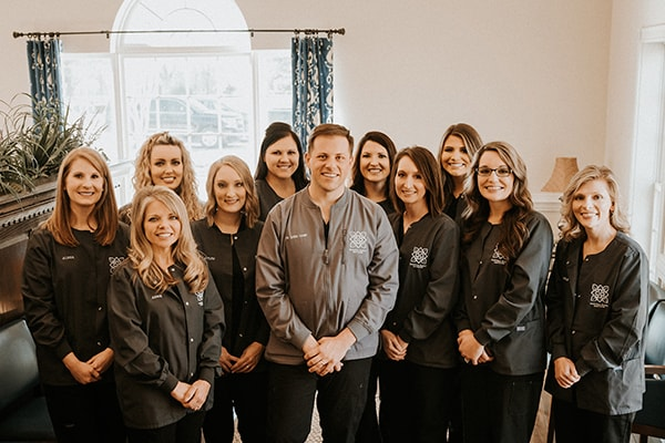The Magnolia Family Dentistry team inside the dental office smiling standing for the photo, all dressed in their work uniform and with their hands clasped under the stomach